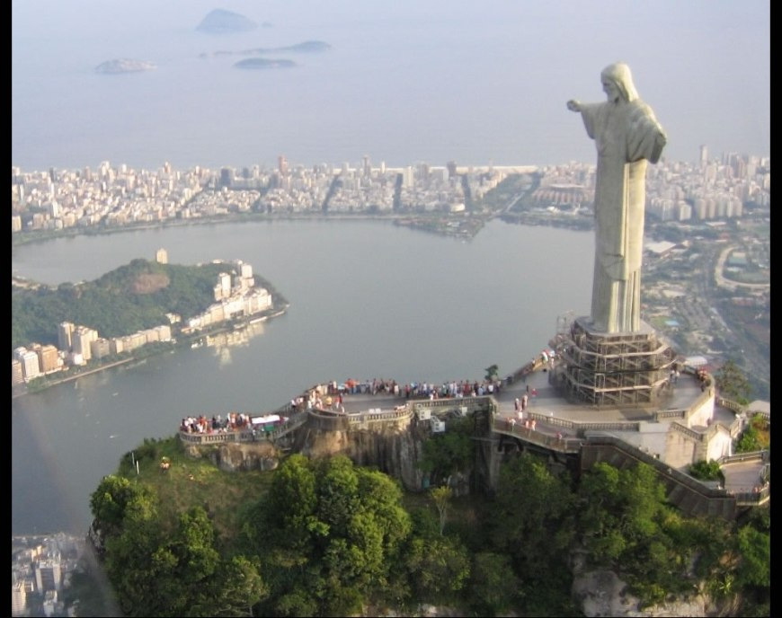 Cristo Redentor statue on top of Corcovado, a mountain towering over Rio de Janeiro. In the background the Ipanema and Leblon beaches separate the lagoon from the Atlantic Ocean