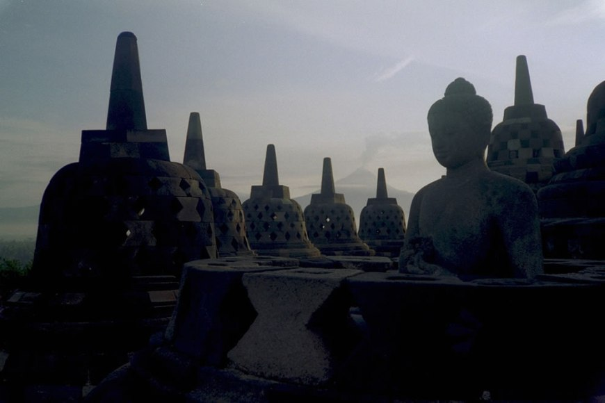 Mt. Merapi erupts from Borobudur with Buddha statue in foreground