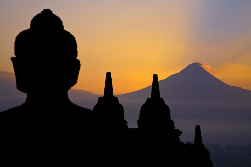 Silent Giants - A Buddha statue of the colossal temple of Borobudur overlooks the Merapi volcano at dawn. Both are silent and full of power