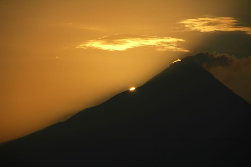 the sun's disc peeps out from the slopes of Gunung Merapi nearby is Borobudur