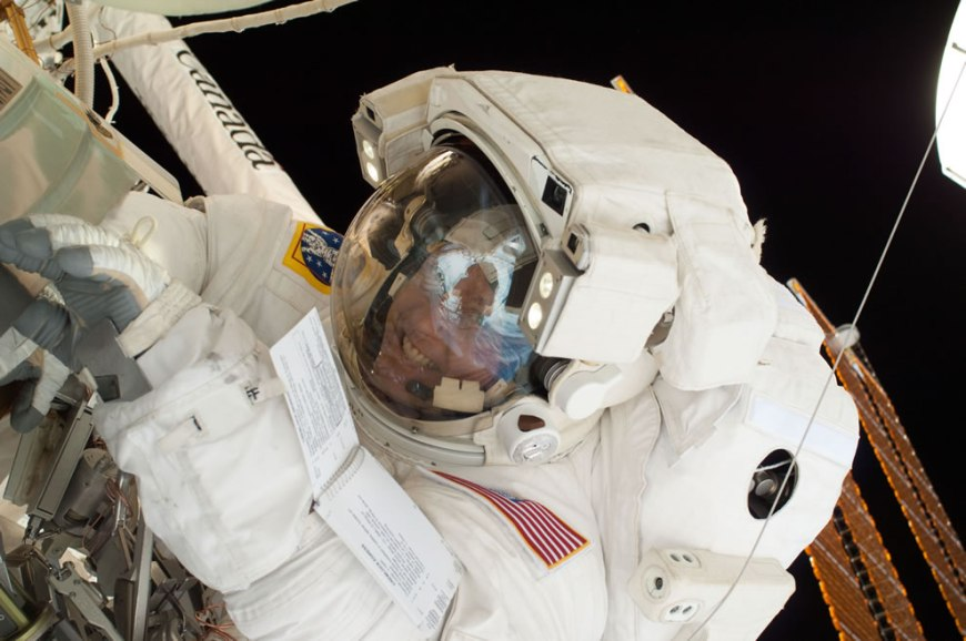 A look into the helmet visor of this astronaut on a spacewalk reveals the easily recognizable smiling countenance of NASA astronaut Michael Fincke