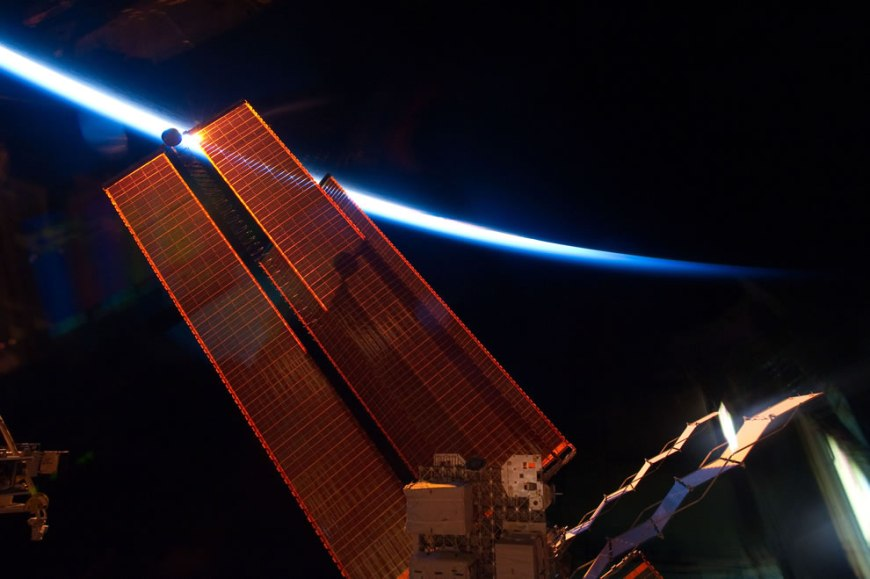 Intersecting the thin line of Earth's atmosphere, International Space Station solar array wings