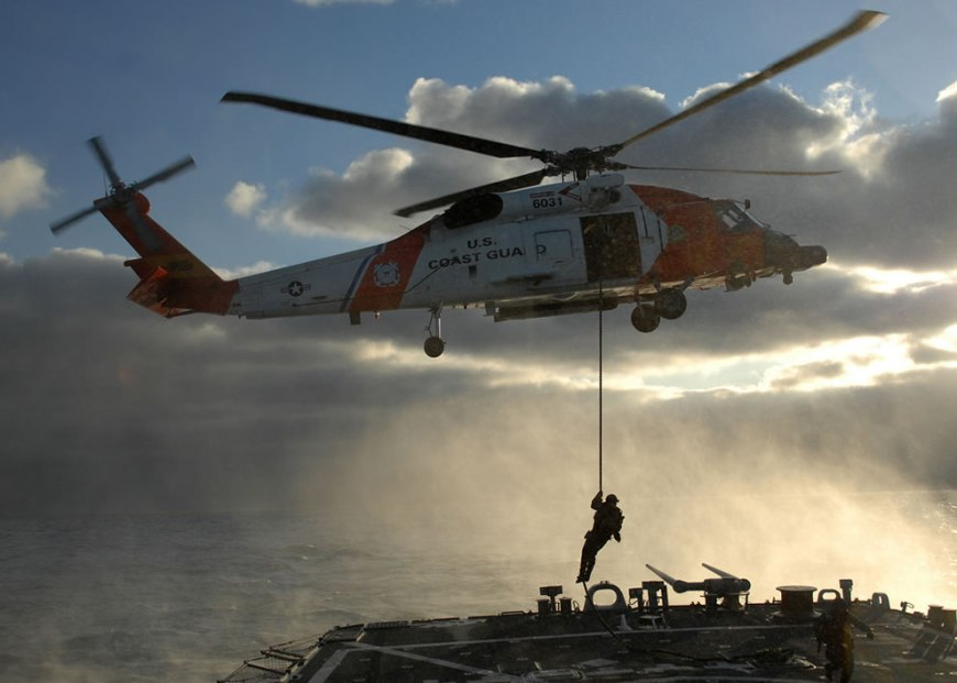 U.S. Coast Guardsman fast-ropes from an HH-60H Seahawk helicopter onto the flight deck of the guided missile destroyer USS Mitscher