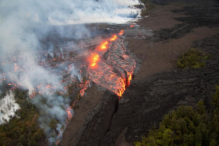 Lava pours from the fissure just west of the base of Pu`u `Ō `ō after daybreak and   cascades out of sight into a deep crack. Lava spatters above the fissure just west of   the base of Pu`u `Ō `ō