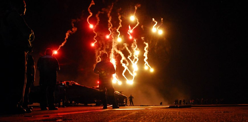 Sailors watch flares light up the sky during a Navy-style fireworks display on the flight deck of the Nimitz-class aircraft carrier USS Ronald Reagan