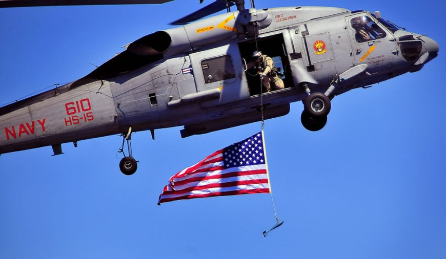 A U.S. Sailor from Explosive Ordnance Disposal Mobile Unit 3 suspends an American flag from an SH-60F Seahawk