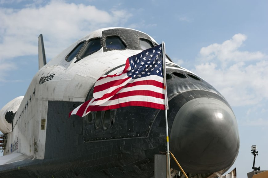 An American flag flaps proudly in the wind in front of space shuttle Atlantis on the Shuttle Landing Facility's Runway 15 at NASA's Kennedy Space Center in Florida. Atlantis' final return from space