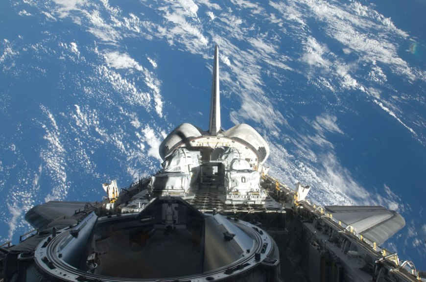 Backdropped by a blue and white part of Earth, a partial view of Space Shuttle Atlantis' payload bay