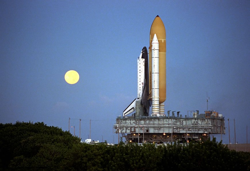 Shortly before dawn, a red-rimmed moon helps to light the way for the Space Shuttle Atlantis as it rolls out to Launch Pad 39A in preparation for launch of Mission STS-86