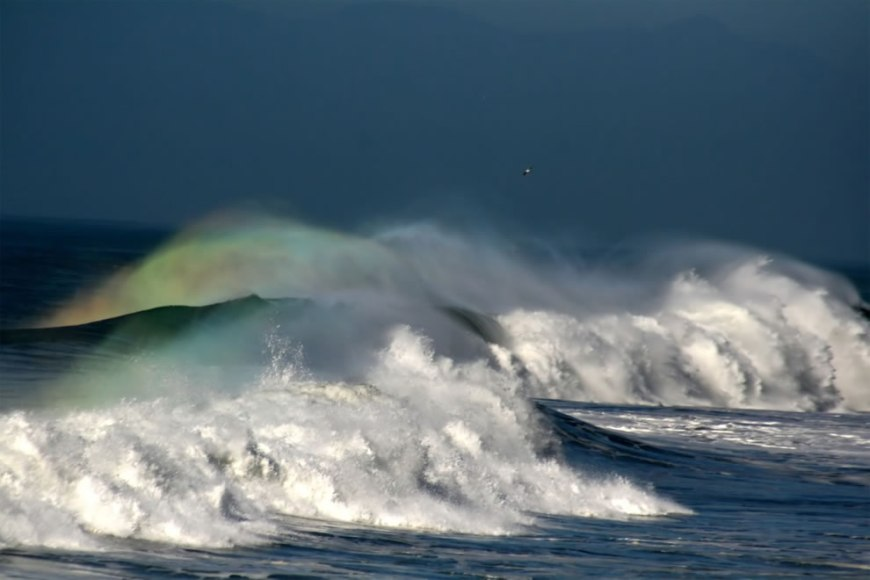 stormy night rainbow in the waves