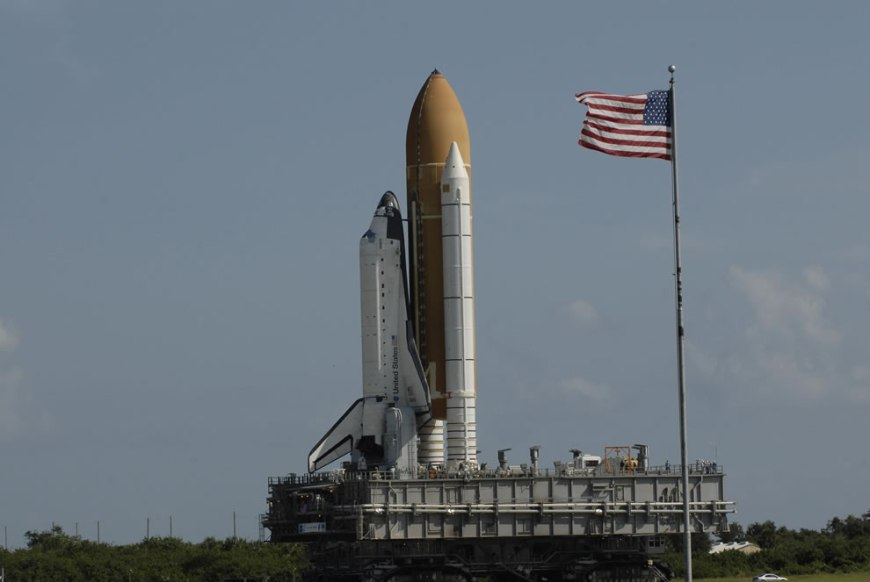 The American flag flies on the NASA News Center grounds at NASA's Kennedy Space Center, giving witness to the passage of space shuttle Atlantis as it rolls out to Launch Pad 39A