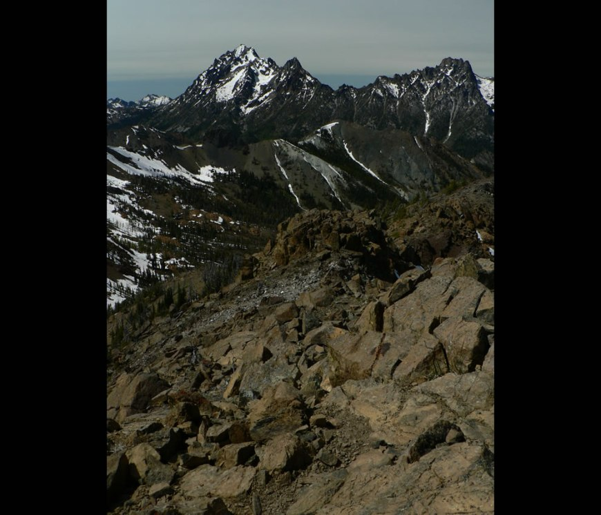 Mount Stuart (9415 feet); Argonaut Peak (8453 feet, right); The Cradle (7467 feet, highest peak on left skyline); Point 6666 feet (right center middle distance); weathered serpentine (foreground)