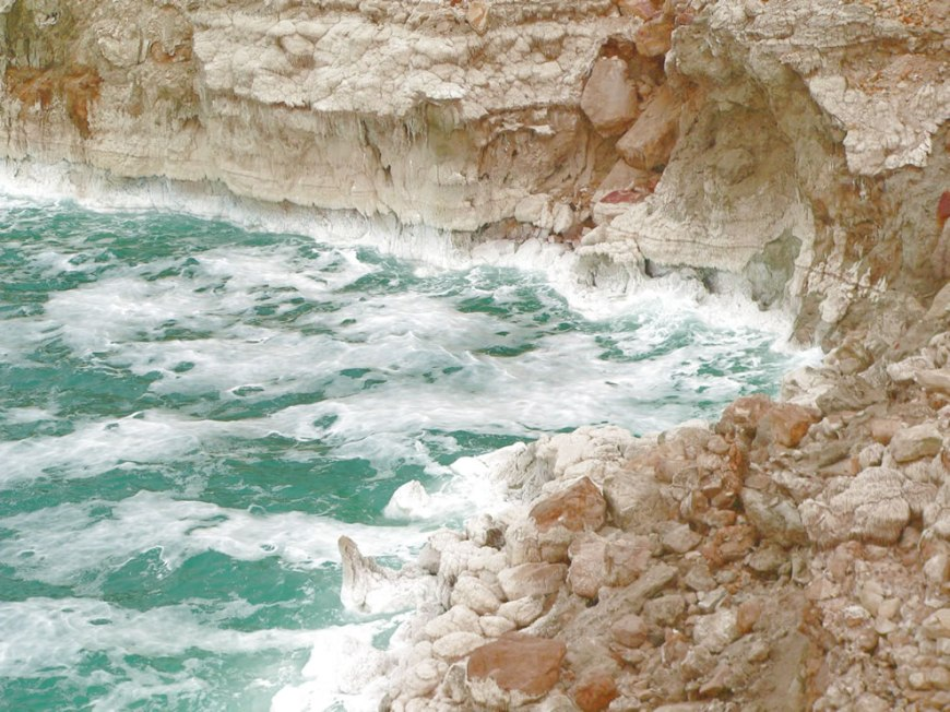 A rough Dead Sea, with salt deposits on cliffs
