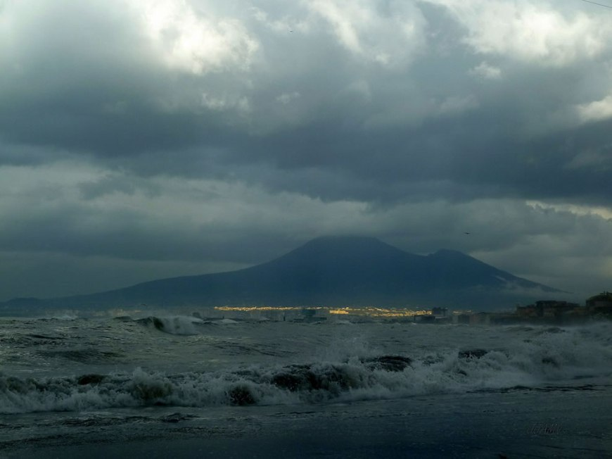 Stormy morning sky, ray of sunlight visible on the foothills of Vesuvio