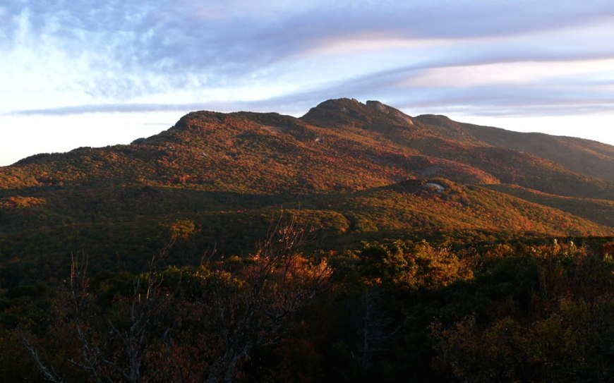 Clouds pour over the Raven Rocks and Calloway Peak, as the rising sun illuminates the brilliant fall foliage on the southeastern face of Grandfather Mountain