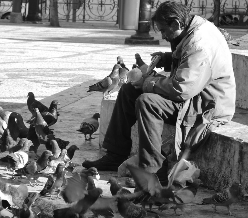 Homeless and hungry, but still sharing his meal with the pigeons