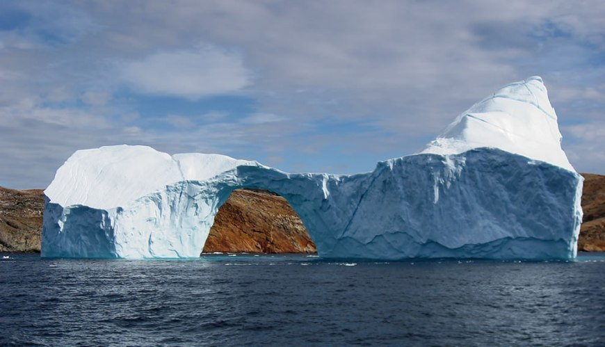 Iceberg with a hole in the strait between Langø and Sanderson Hope south of Upernavik, Greenland
