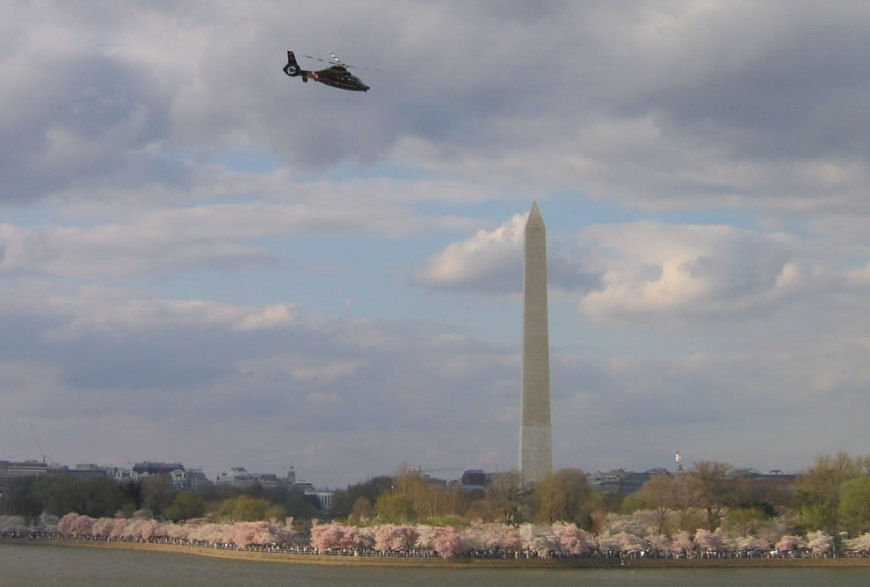 Maryland State Police helicopter above the Tidal Basin in Washington D.C., USA. Image was captured during the Cherry Blossoms and includes the Washington Monument