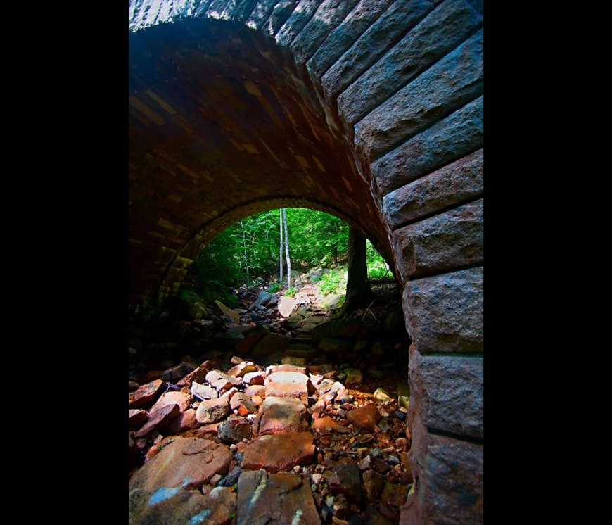 A trail passing underneath one of the carriage road bridges