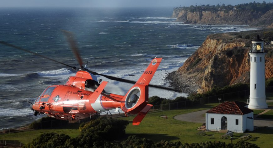 A U.S. Coast Guard MH-65C Dolphin helicopter crew assigned to Air Station Los Angeles conducts a flyover of the Point Vicente Lighthouse as part of the memorial service