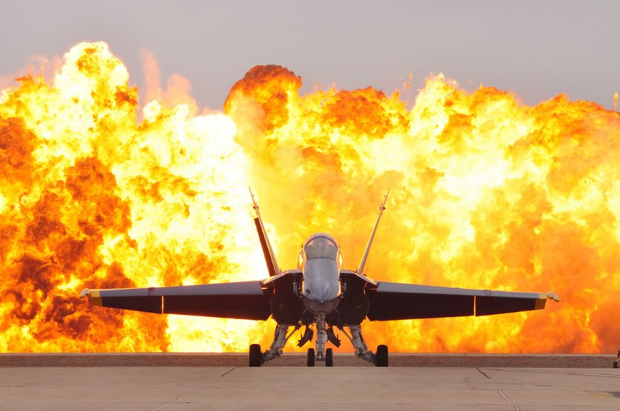 An FA 18 Hornet aircraft from the U.S. Navy's Flight Demonstration Squadron Blue Angels sits on the flight line as a wall of fire detonates behind it