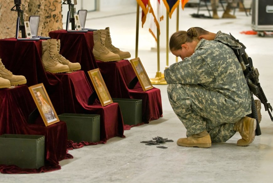 U.S. Army soldiers pay final respects during a memorial service, honoring three fallen comrades killed in action from a rocket attack