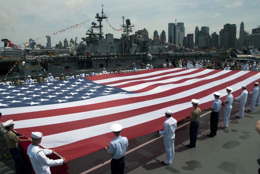 U.S. Navy, Marine Corps and Coast Guard personnel unfurl an American flag on the flight deck of the Intrepid Sea, Air & Space Museum at a Memorial Day ceremony during Fleet Week New York