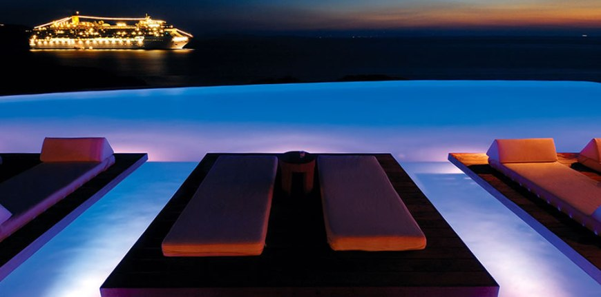 dreaming the night away, infinity pool at night overlooking brightly lit ship infinity pool