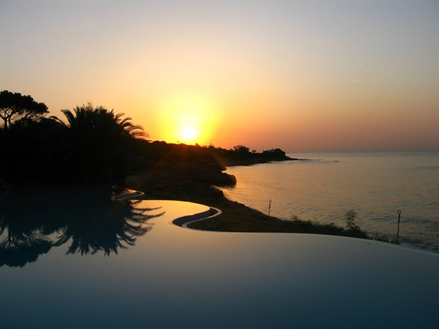 Sunrise over the amazing infinity pool in the private beach at hotel costa dei fiori, on the south coast of Sardinia