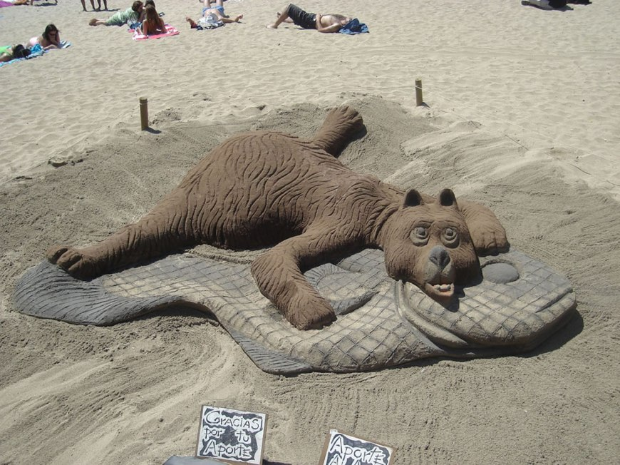 bear on a fish rug animal sand sculpture  sandpainting